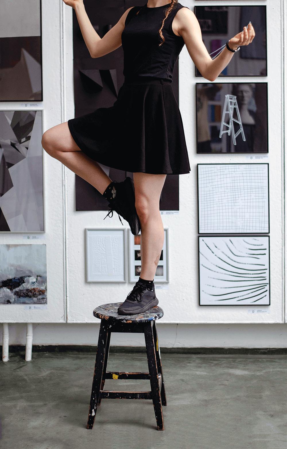 Studentka w czarnej sukience stoi na stołku i balansuje na jednej nodze. W tle widać wiele prac plastycznych: grafik, fotografii i kolaży wyeksponowanych na ścianie.