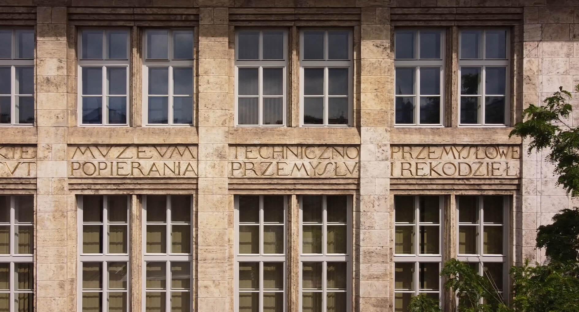 """Fragment kamiennej fasady budynku Wydziału. Między dwoma rzędami okien widoczny fragment wykutego napisu o treści """"Muzeum Techniczno-Przemysłowe popierania przemysłu i rękodzieł"""