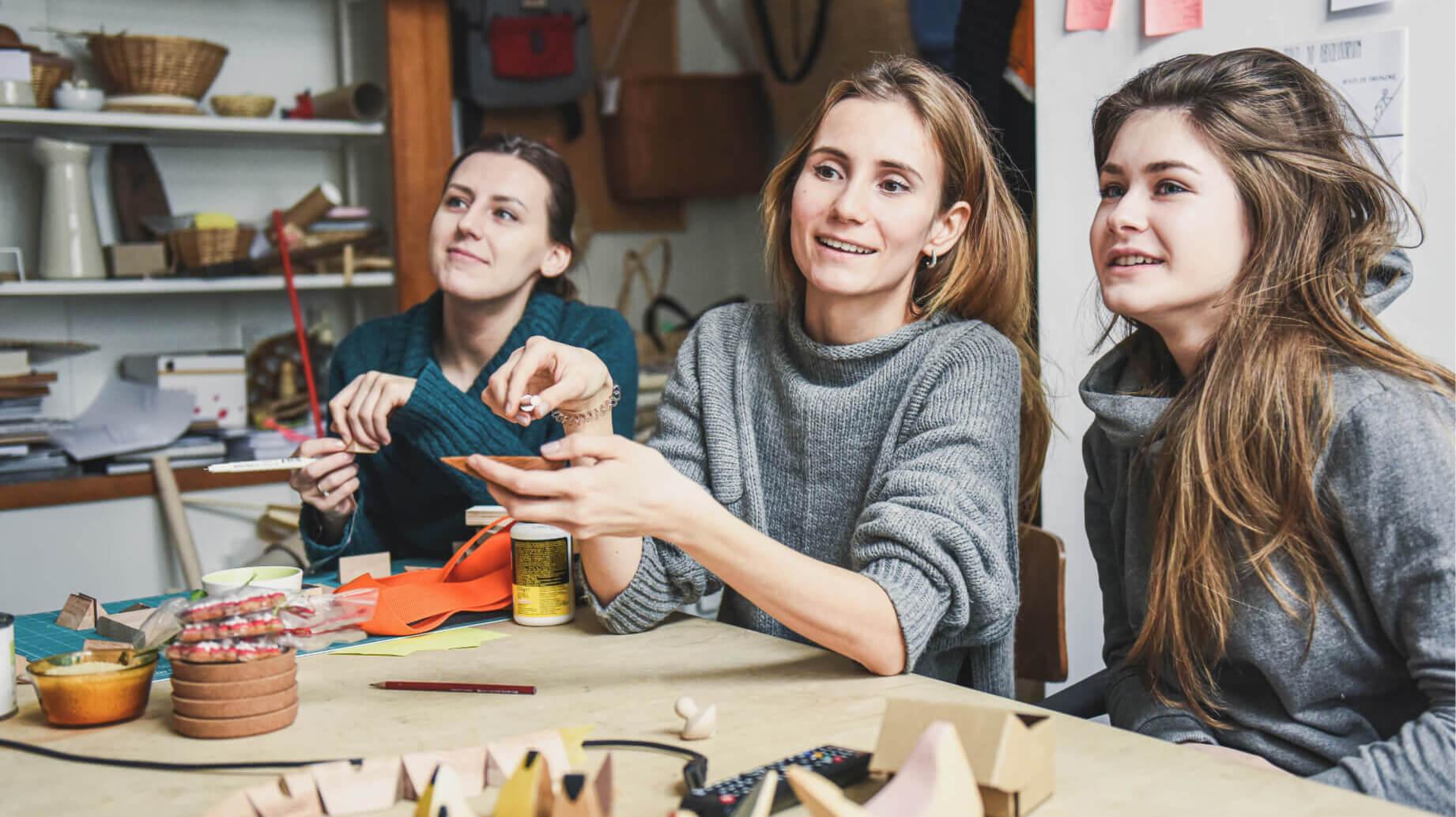 Trzy studentki podczas zajęć. Siedzą przy drewnianym stole na którym leżą fragmenty drewnianych zabawek i akcesoria do modelowania. W tle drewniane półki z plecionymi koszami, ceramiką, obiektami ze skóry.