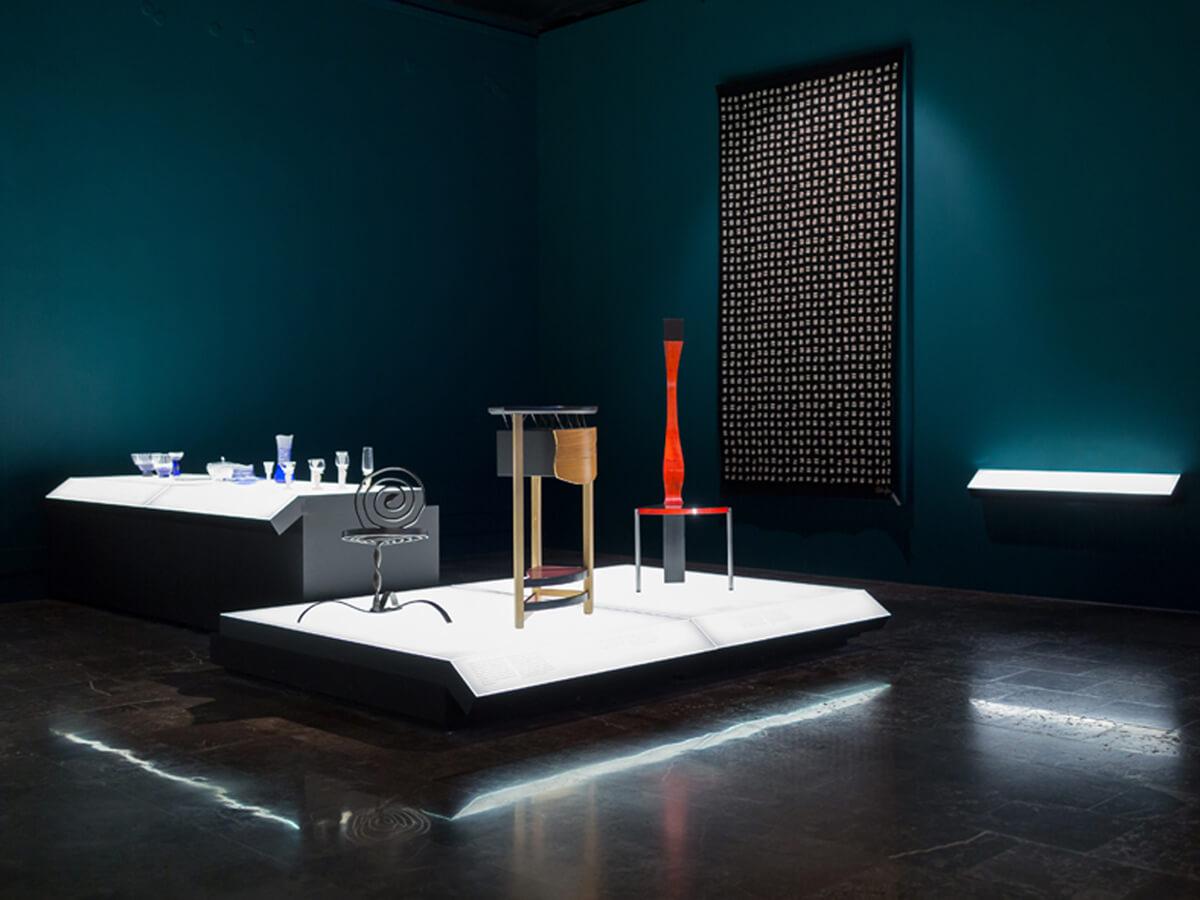 Eksponaty muzealne umieszczone na dwóch podświetlanych platformach. Na pierwszej stoją: obiekt z kutego metalu, drewniany stolik i fotel. Na długiej platformie stoi zestaw szklanych naczyń. Ściany pomieszczenia są ciemnoniebieskie.