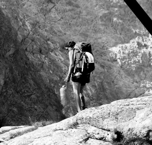 Czarno-biała fotografia Małgosi Kęckiej stojącej na skale, z plecakiem na plecach i śpiworem w dłoni. W tle ściana skalna.