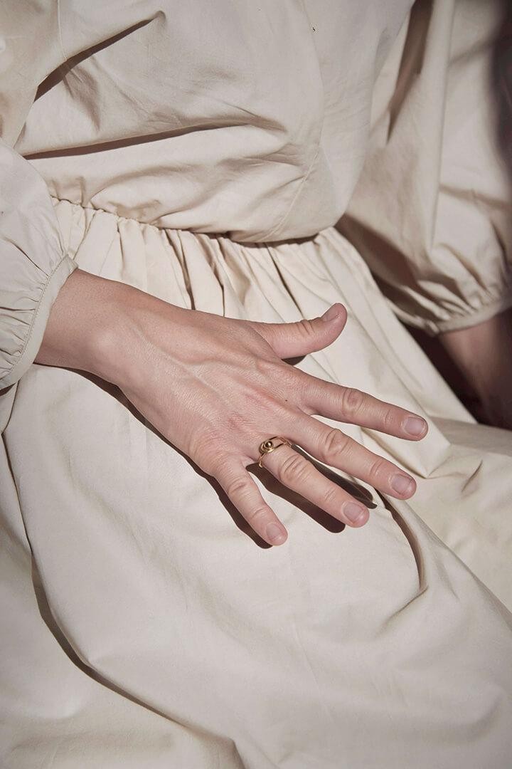 Wyciągnięta dłoń a na niej złoty pierścionek, w tle fragment postaci w białej drapowanej sukni